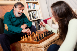 elderly man and his caregiver playing chess